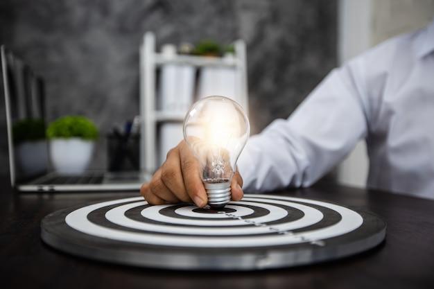Ideia de negócio bem-sucedida e conceito de inovação criativa, close-up do homem de negócios segurando a lâmpada na placa de destino na mesa