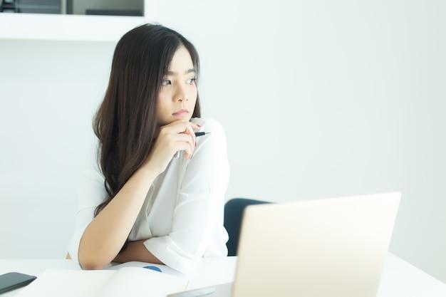 Ideia de sorriso e de pensamento asiática nova da mulher de negócio sobre o trabalho na mesa no escritório moderno.