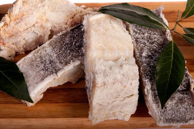 Ideia de um grupo do bacalhau salgado cortado isolado em um fundo branco.