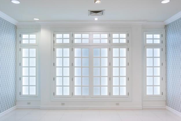 Ideia de um interior escandinavo vazio branco da sala com assoalho branco e grande parede e paisagem branca na janela.