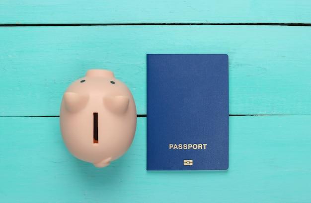 Ideia de viagem ou emigração. passaporte com cofrinho na superfície de madeira azul. vista do topo