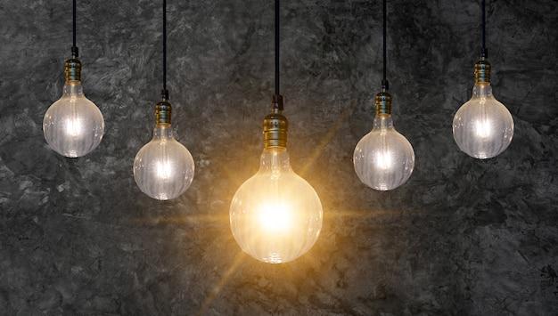 Idéia diferente das lâmpadas muitas lâmpadas são dispostas em uma fileira e uma delas é acesa. idéia de conceito