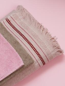 Ideia do close-up de toalhas de terry macias de cores diferentes no fundo rosa. vista do topo.