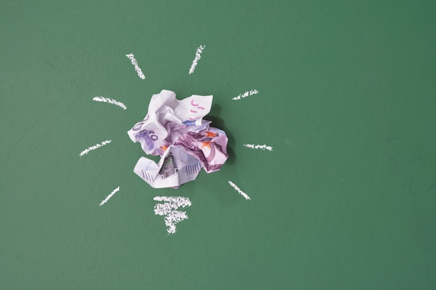 Idéia do conceito de economizar dinheiro. notas de dólar de papel amassadas na forma de lâmpadas no fundo verde do quadro de giz k
