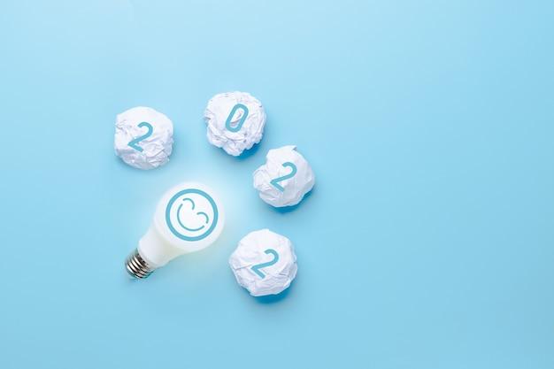 Ideia e criativa em 2022, lâmpada com número de ano novo em fundo azul