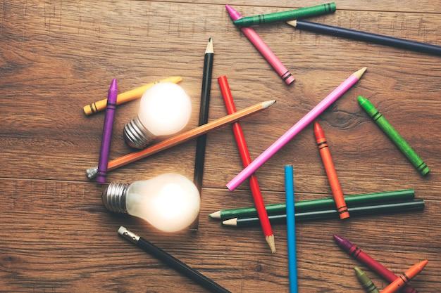Ideia e muitos lápis coloridos na mesa de madeira