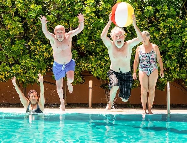 Ideia engraçada de casais de idosos brincando na água azul e transparente da piscina. homem pula na piscina com uma grande bola inflável