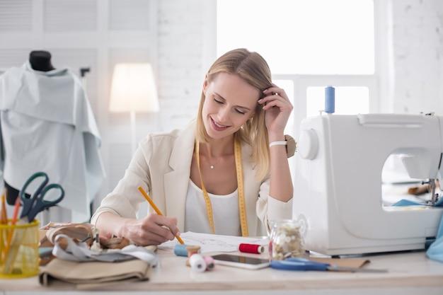 Idéia genial. estilista feminina atraente tocando o cabelo enquanto desenha