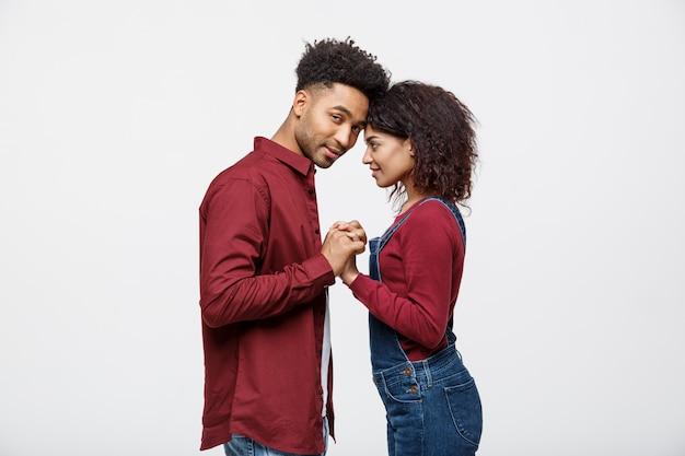 Ideia lateral de pares novos bonitos do americano africano nas camisas clássicas que prendem as mãos.