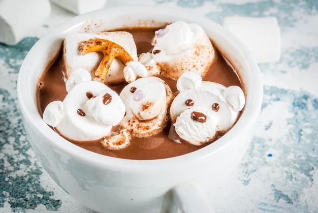Idéia para um lanche infantil de natal, chocolate quente com ursinhos de pelúcia e marshmallow de veado. em uma superfície clara, copie o espaço