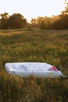 Idéia para uma sessão de fotos na natureza. cama com roupa de cama em um campo no verão ao pôr do sol