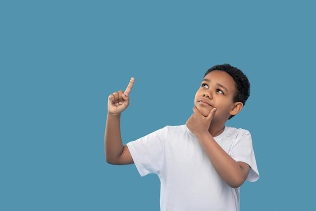 Idéia, pensamento. menino pensativo de pele escura na escola primária olhando para cima apontando o dedo em pé em uma foto de estúdio
