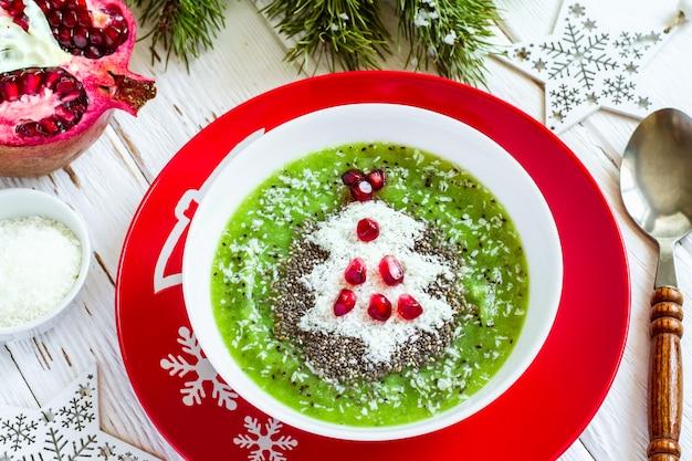 Ideia saudável de comida de natal. smoothies verdes decorados com árvore de natal, feitos de coco e romã. conceito de comida saudável ou infantil