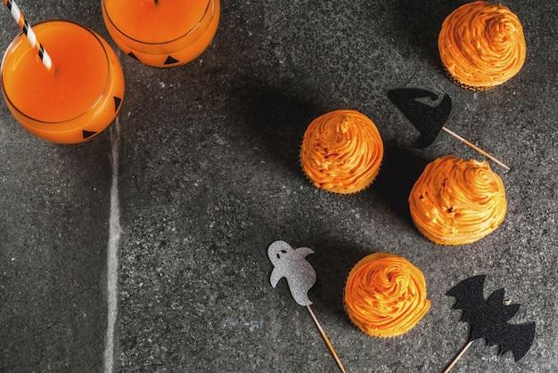 Idéia simples de deleite infantil engraçado para o halloween: bolos de abóbora com creme, com decorações em forma de símbolos de férias - fantasma, bruxa, morcego. em um preto, copyspace
