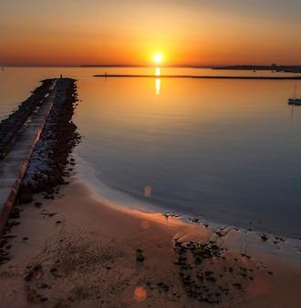 Ideia sonhadora de um cais do disjuntor da maré no por do sol.