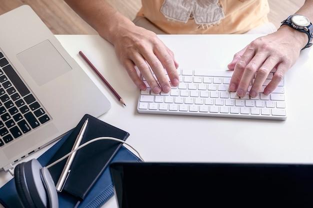 Ideia superior da mão do homem que datilografa no teclado branco ao trabalhar em casa.