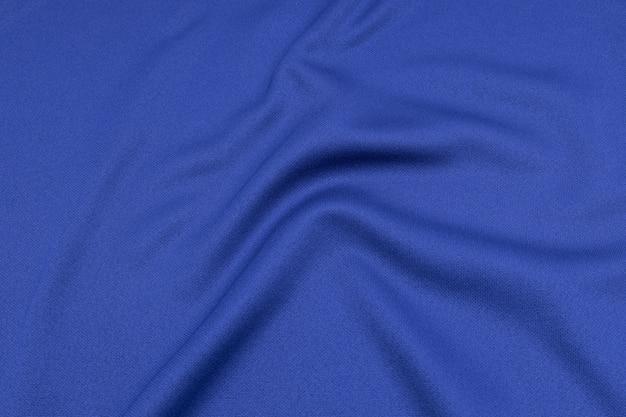 Ideia superior da textura da tela da roupa de esporte da superfície de matéria têxtil de pano. camisa azul do futebol com copyspace.