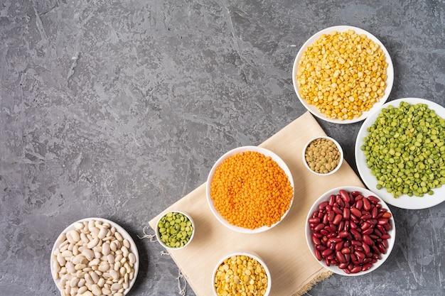 Ideia superior da variedade das ervilhas, das lentilhas, dos feijões e das leguminosa sobre o fundo cinzento.
