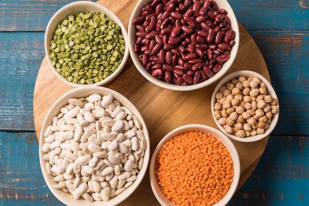 Ideia superior da variedade das ervilhas, das lentilhas, dos feijões e das leguminosa sobre o fundo de madeira azul.