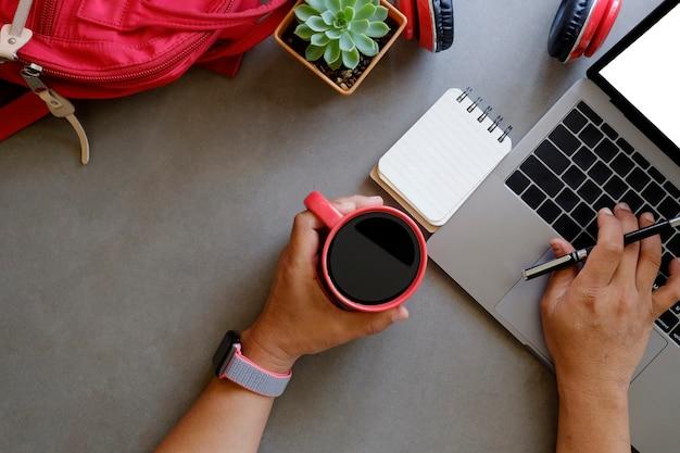 Ideia superior das mãos usando o laptop e guardando um copo de café com saco e fones de ouvido.