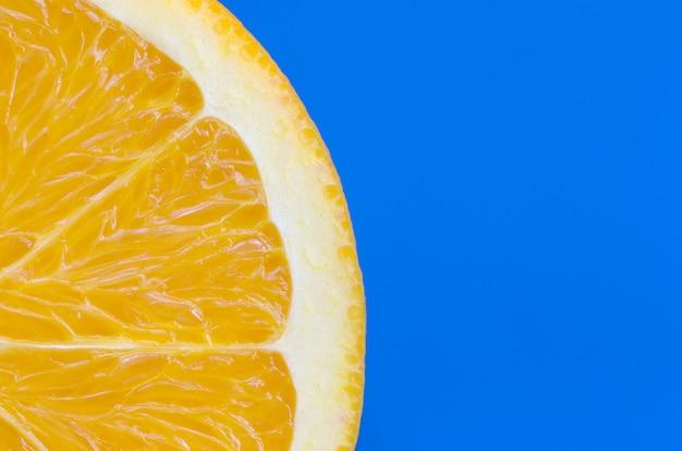 Ideia superior de uma fatia alaranjada de uma fruta no fundo brilhante na cor azul. uma imagem saturada de textura cítrica