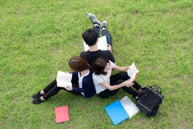 Ideia superior do grupo de estudantes asiáticos que sentam-se junto no parque.