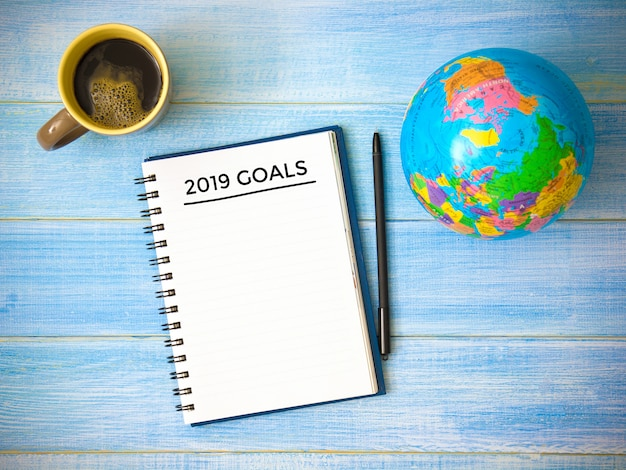Ideia superior dos objetivos da escrita do caderno 2019 anos na tabela de madeira azul.