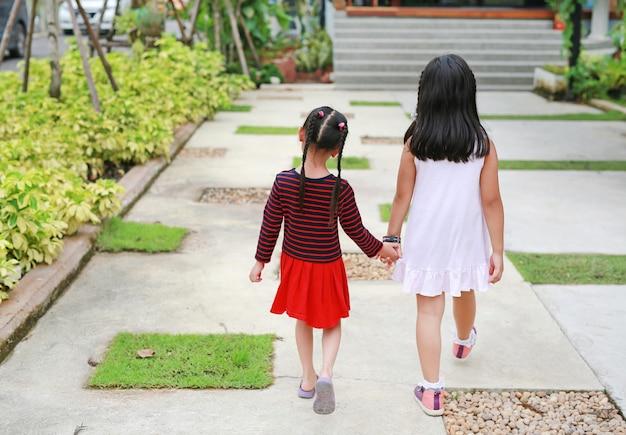 Ideia traseira das mãos da posse da irmã com as crianças pequenas que andam no jardim da estrada.