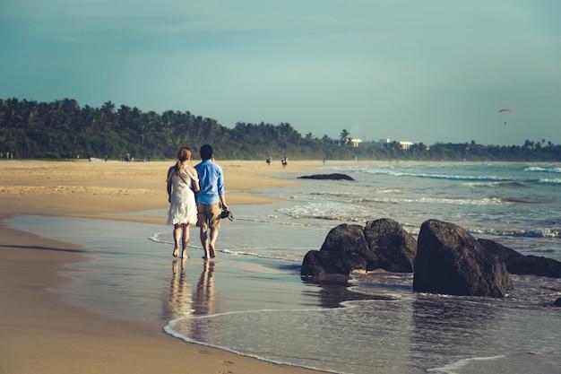 Ideia traseira dos pares novos felizes que andam em uma praia tropical abandonada. foto de tonificação
