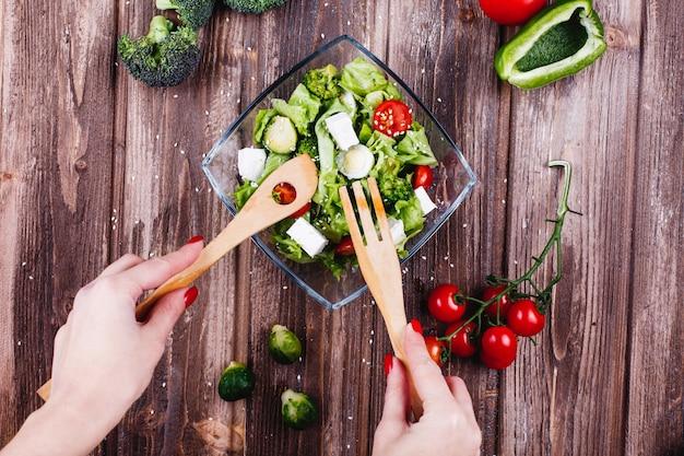 Idéias de almoço ou jantar. mulher sacode a salada fresca de vegetação, abacate, pimenta verde