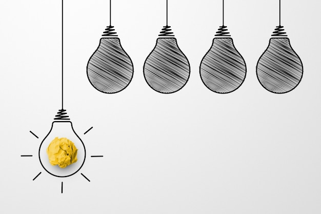 Ideias de pensamento criativo e conceito de inovação. resíduos de papel bola de cor amarela com o símbolo da lâmpada no fundo branco