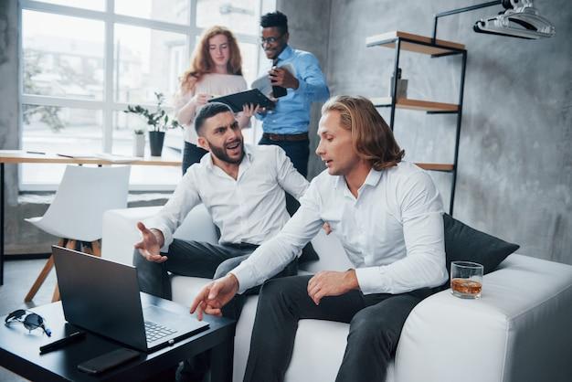 Idéias loucas. grupo de trabalhadores de escritório multirracial em roupas formais falando sobre tarefas e planos