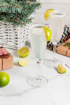Idéias para bebidas de natal e ano novo. cocktails champagne margarita, guarnecidos com limão e sal. na mesa branca com decorações de natal, copyspace