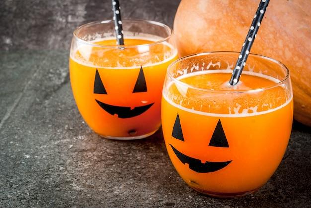 Idéias para crianças e festa de doces de halloween. cocktail de abóbora laranja em copos, decorado com uma lanterna de abóbora, em uma mesa de pedra preta. copie o espaço