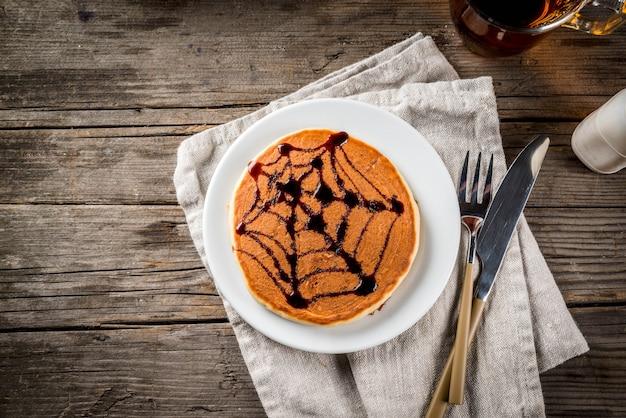 Idéias para o café da manhã são halloween, comida para crianças. panquecas de torta de abóbora decoradas com calda de chocolate em um estilo tradicional - teia de aranha, aranha, lanterna de jack. na mesa rústica de madeira, copie o espaço