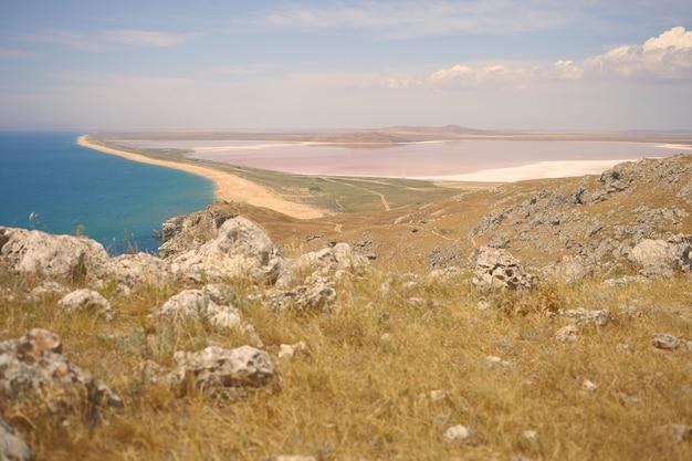 Idílica bela paisagem de verão do vale, o mar turquesa calmo e a superfície rochosa no topo da colina. aproveitando o dia de sol na natureza selvagem. vista do mar, montanhas, atração turística e conceito de aventura