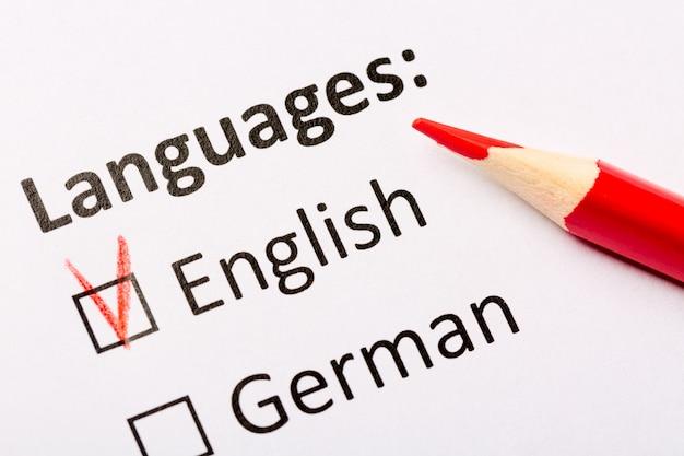 Idiomas com caixas de seleção em inglês e alemão com lápis vermelho.