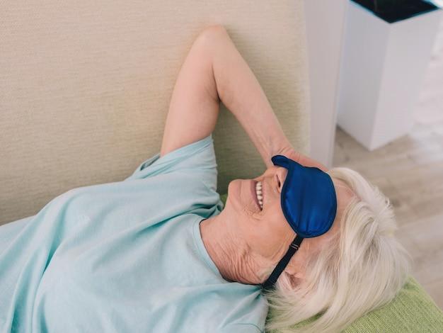 Idosa, alegre, caucasiana, elegante, mulher, cabelos grisalhos, deitada com as pernas para cima na máscara do sofá