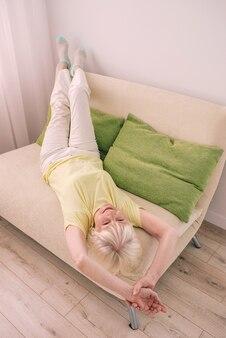 Idosa, alegre, caucasiana, elegante, mulher, cabelos grisalhos, deitada com as pernas para cima no sofá