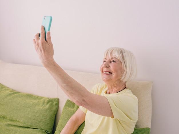 Idosa alegre caucasiana elegante mulher com cinza feliz para conversar com a família ou amigo
