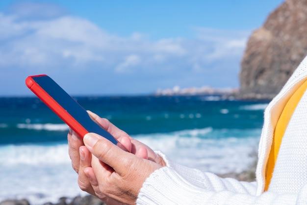 Idosa aproveitando as férias na praia em um dia de vento, lendo uma mensagem em seu smartphone