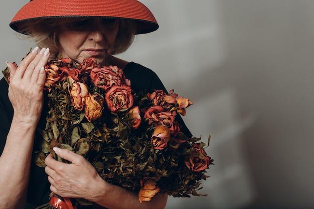 Idosa chateada segurando um buquê de flores de rosas secas e murchas