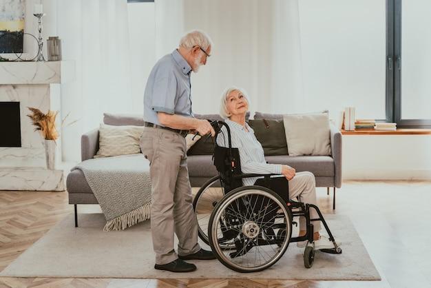 Idosa com deficiência em cadeira de rodas casal sênior em casa parceiro voltando do hospital