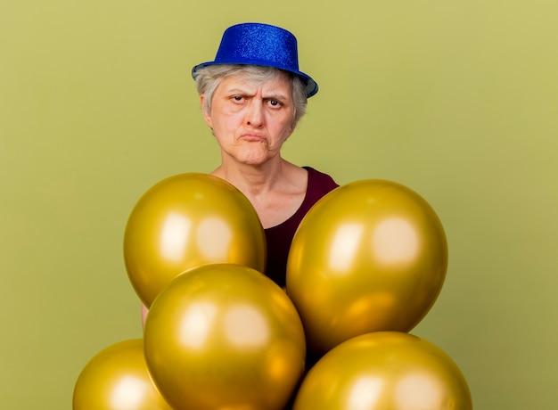 Idosa decepcionada usando suportes para chapéus de festa com balões de hélio isolados em uma parede verde oliva com espaço de cópia