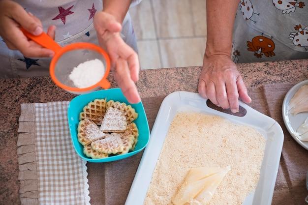 Idosa e mulher em casa cozinhando peixe na cozinha - muito focado em casa - mulher madura e caucasiana dos anos 60 - mulher aposentada - com a mão na mesa preparando o peixe e a sobremesa