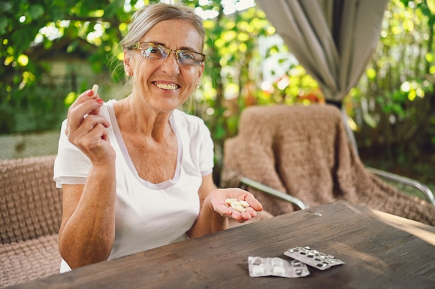 Idosa feliz sênior idosa em óculos de grau leva remédio drogas vitaminas pílulas ao ar livre no jardim. conceito de estilo de vida para idosos de saúde