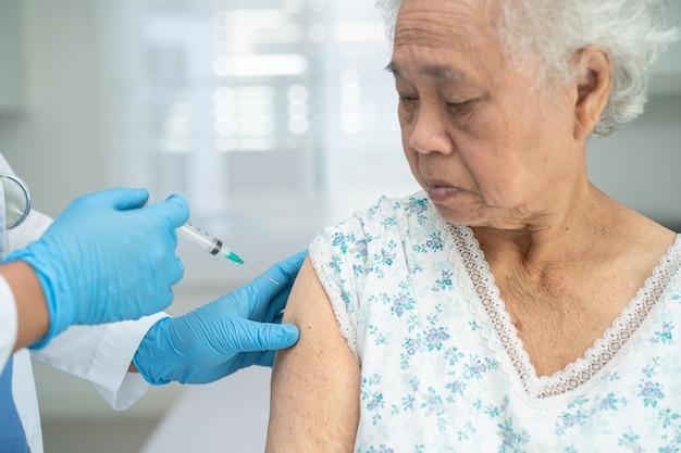 Idosa idosa asiática recebendo vacina contra covid19 ou coronavírus pelo médico