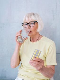 Idosa idosa de óculos segurando comprimidos e um copo de água cuidados de saúde da idade