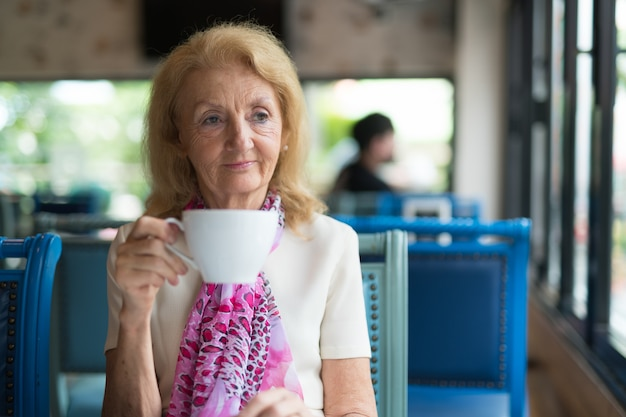 Idosa tomando café e olhando pela janela