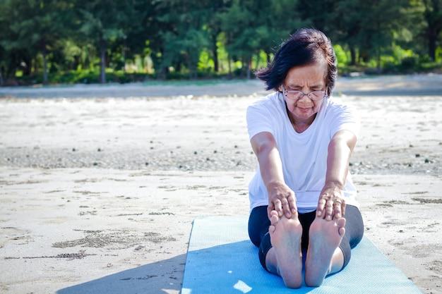 Idosas se exercitando na praia à beira-mar ar puro, corpo forte